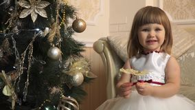 Little girl in festive dress with a golden butterfly near the Christmas tree stock footage
