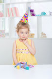 Little girl in a festive hat. Charming little girl in a festive hat. child in yellow dress smiling Royalty Free Stock Photo