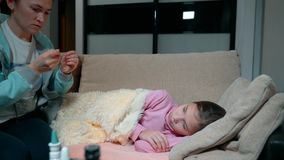 A little girl with fever lies on the couch. The mother measures the temperature of her daughter`s body with the help of stock video
