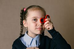 Little girl with Fidget Spinner held up to his eyes royalty free stock image