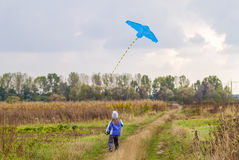 Little girl on field gravel road path running with a kite. Royalty Free Stock Image