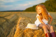 Little girl in a field with hay rolls Royalty Free Stock Image