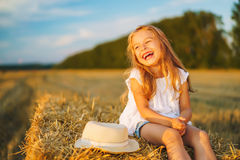 Little girl in a field with hay rolls. At sunset Stock Photos