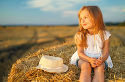 Little girl in a field with hay rolls. At sunset Stock Images