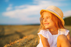 Little girl in a field with hay rolls. At sunset Stock Photography