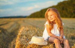 Little girl in a field with hay rolls. At sunset Stock Photo