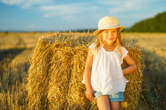 Little girl in a field with hay rolls. At sunset Royalty Free Stock Photos