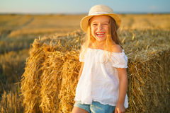 Little girl in a field with hay rolls Royalty Free Stock Photography