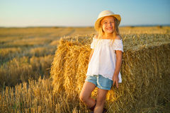 Little girl in a field with hay rolls Royalty Free Stock Images