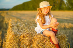 Little girl in a field with hay rolls Stock Image