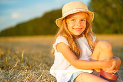 Little girl in a field with hay rolls Stock Images