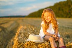 Little girl in a field with hay rolls Royalty Free Stock Photo