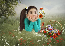 The little girl in the field with poppies. Little girl with dreamy eyes, lying in the field with poppies on sunny summer day stock photography