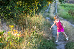 Little girl on a field road playing with fire Royalty Free Stock Photo