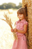 Little girl on the field with wheat bale of hay Stock Photos