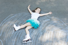 Little girl figure skating at imaginary skating rink arena. Laying down on asphalt after drawing rink arena with chalk, dreaming of becoming professional ice Stock Images