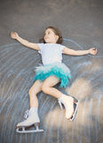 Little girl figure skating at imaginary skating rink arena. Laying down on asphalt after drawing rink arena with chalk, dreaming of becoming professional ice Stock Photos