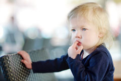 Little girl with finger in her mouth. Cute little girl sucking her finger Stock Images