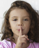Little girl with finger on lips Stock Photos