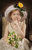 Little girl with finger on lips. Portrait of beautiful little girl in hat with finger on lips Stock Photo