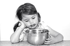 Little girl finished to eat big bowl of chocolate cream Stock Images