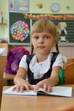 Little girl is first class at school. Sits by the table royalty free stock photography