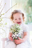 Little girl with first spring flowers at home Stock Photo