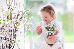 Little girl with first spring flowers at home. Little girl playing with first spring flowers at home. Child watering house plant. Toddler with cherry blossom stock photos