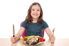 Little girl with fish for lunch Stock Photos