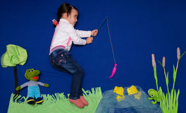 Little girl fishes Stock Photos