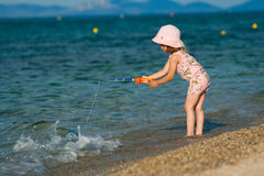 Little girl fishing. Little pretty girl trying to catch fish in the blue sea. Playing at sunset stock images