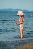 Little girl fishing. Little pretty girl trying to catch fish in the blue sea. Playing at sunset stock photography