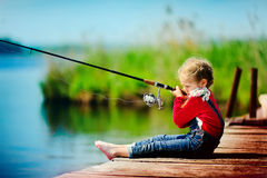 Little girl fishing from dock on lake stock photography