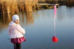 Little girl fishing from dock on lake. Stock Images