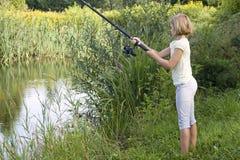 Little girl fishing on lake Stock Images