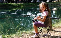 Little girl with the fishing rod on the shores of Lake fishing 1 Stock Photos