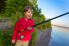 Little girl fishing with spinning Royalty Free Stock Photo