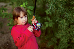 Little girl fishing with spinning Stock Image