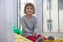 Little girl   sitting by   window in   cozy room. stock images