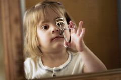 Little girl fixing her make up. A little girl curling her eye lashes Stock Photo