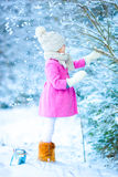 Little girl with flashlight and candle in winter on Christmas eve outdoors Royalty Free Stock Image