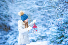 Little girl with flashlight and candle in winter day outdoors Royalty Free Stock Image