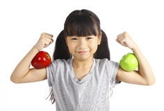 A little girl flexes her muscle while showing off the apple that made her strong and healthy Stock Photo