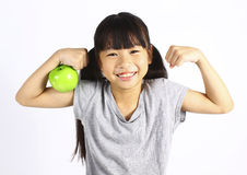 A little girl flexes her muscle while showing off the apple Royalty Free Stock Photo
