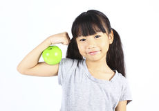 A little girl flexes her muscle while showing off the apple. Stock Image