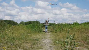 Little girl flies a kite stock footage