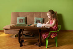 Little girl flips through an album Stock Photos
