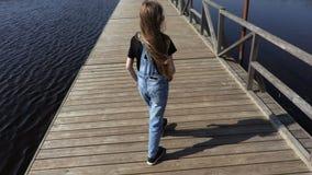 Little girl on floating bridge in lake stock video