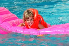 Little girl floats on an inflatable mattress Stock Images
