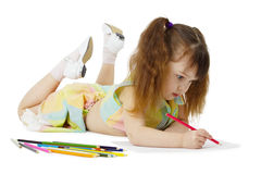 Little girl on floor drawing with crayons Royalty Free Stock Images